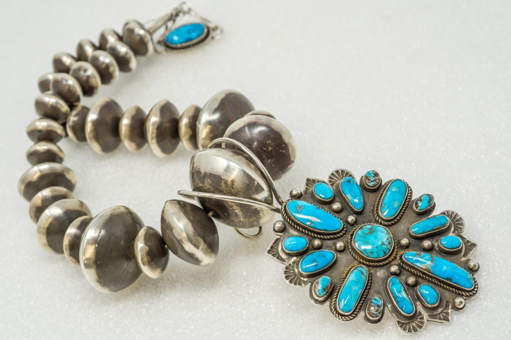 Oversize Navajo pearls of sterling silver hold a large pendant of oxidized silver with cabochons of turquoise; by Tommy Jackson