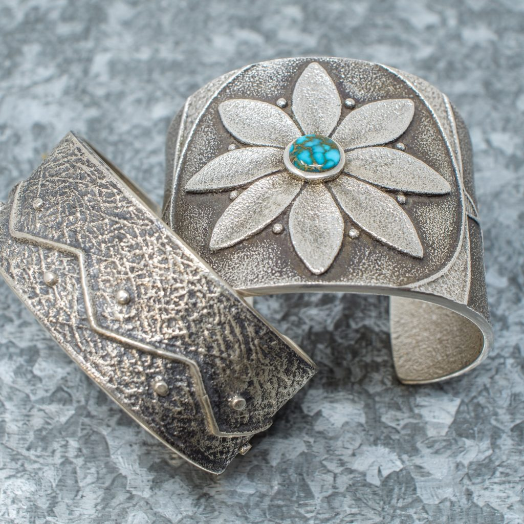 Tufa stone-cast bracelets with flower design by Navajo designers Gary Custer and Rebecca Begay